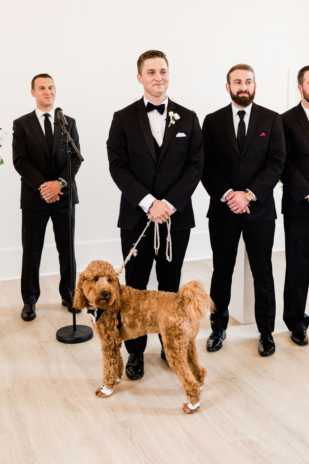 A groom smiling with his dog