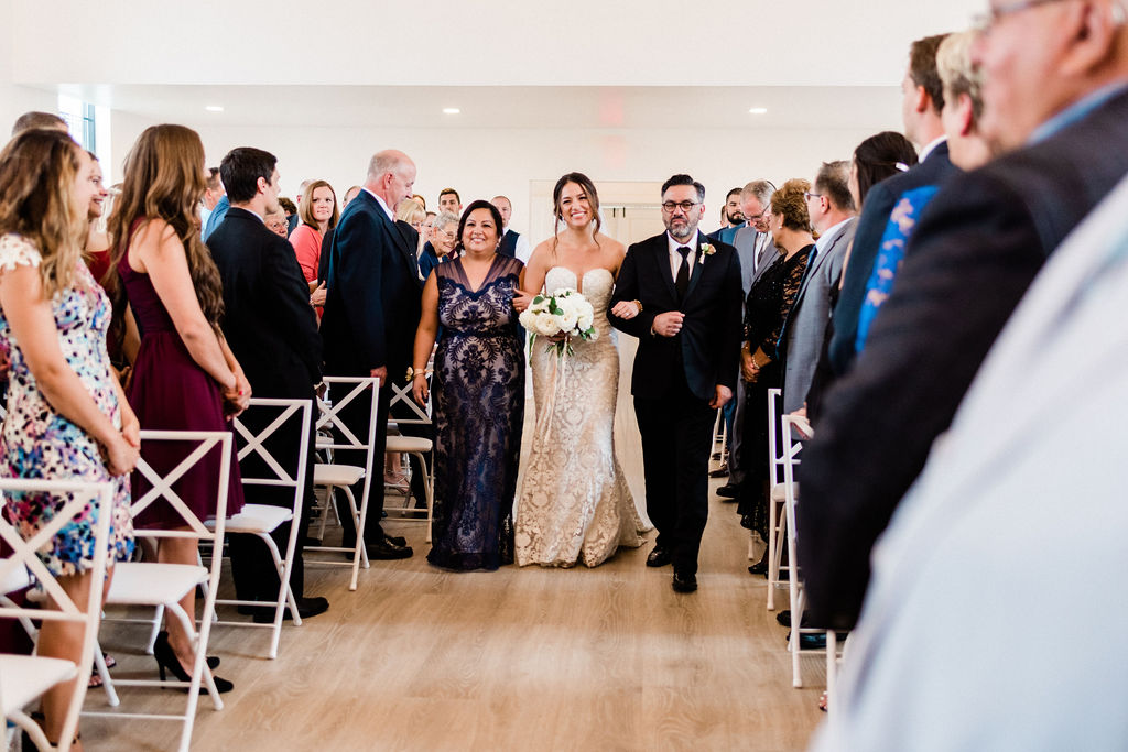 Bride walking with her parents down the aisle during her Kalamazoo, Michigan wedding