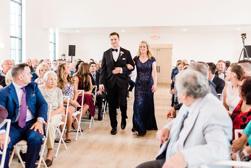 Groom walking his mom down the aisle during his Kalamazoo, Michigan wedding