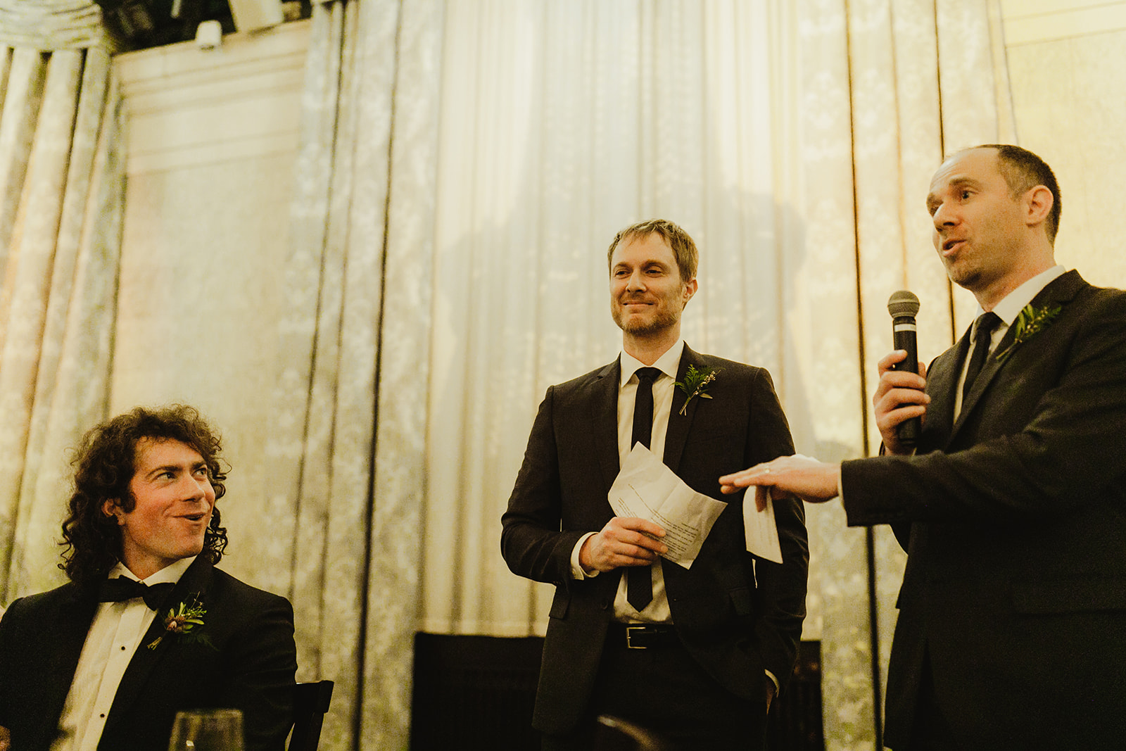 A groom and his best men sharing speeches during his wedding