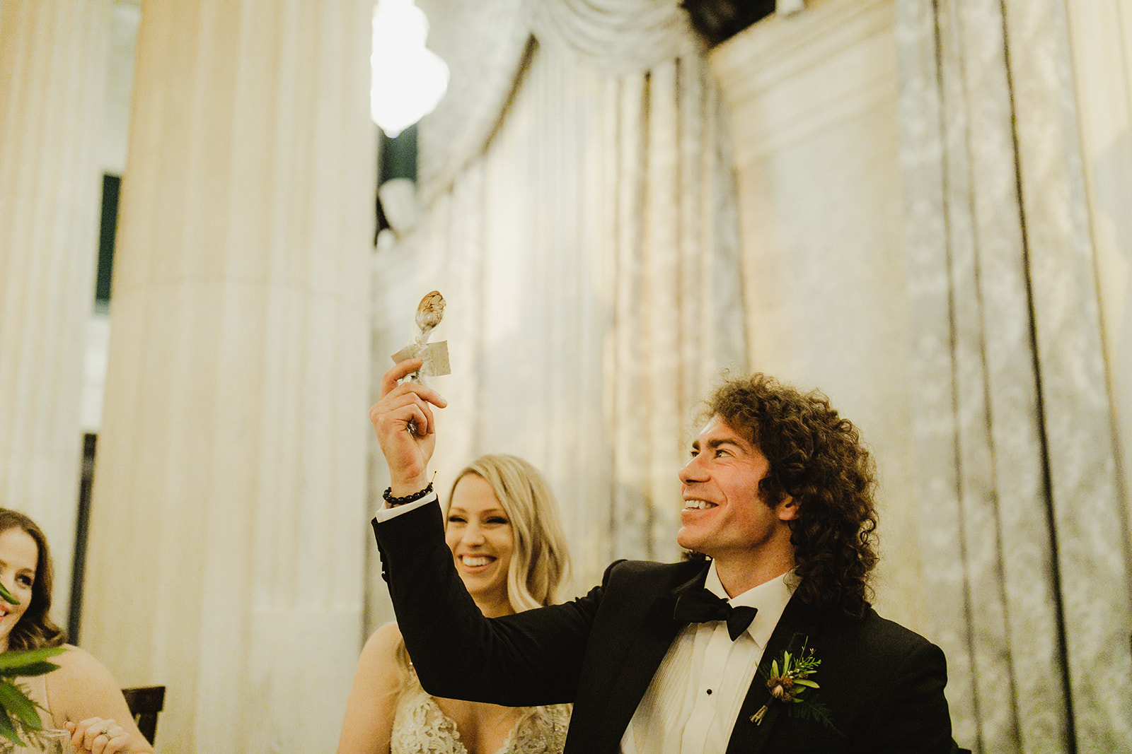 A groom smiling and holding up a spoon