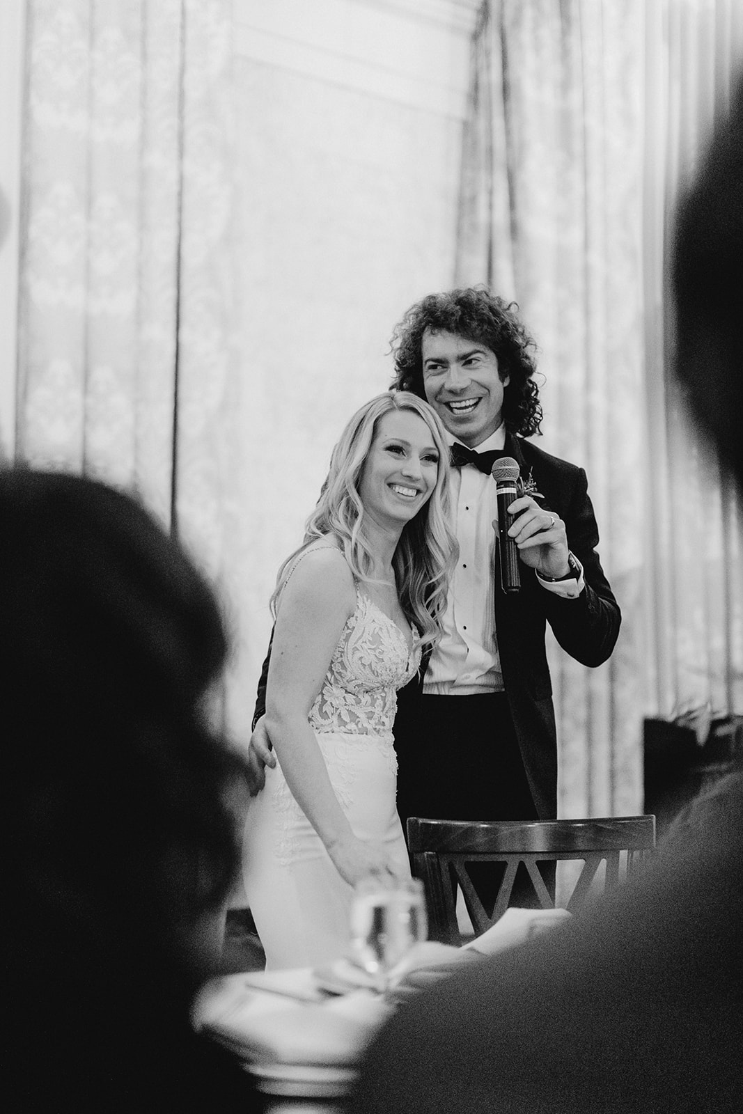 A couple smiling during speeches at their Grand Rapids, Michigan wedding