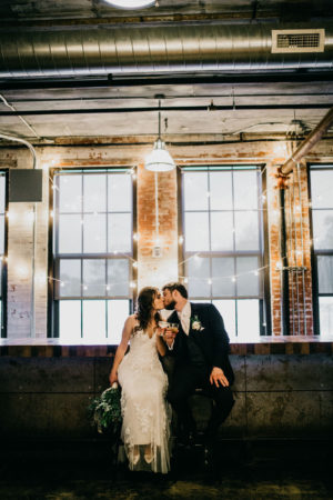A couple kissing during their Journeyman Distillery wedding