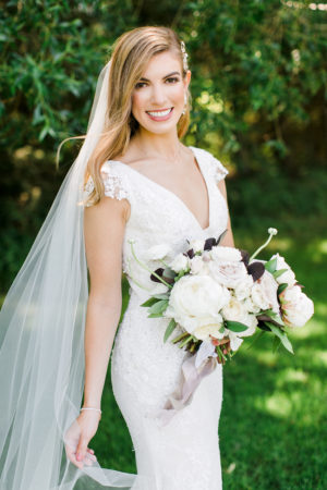 A bride smiling with her bouquet