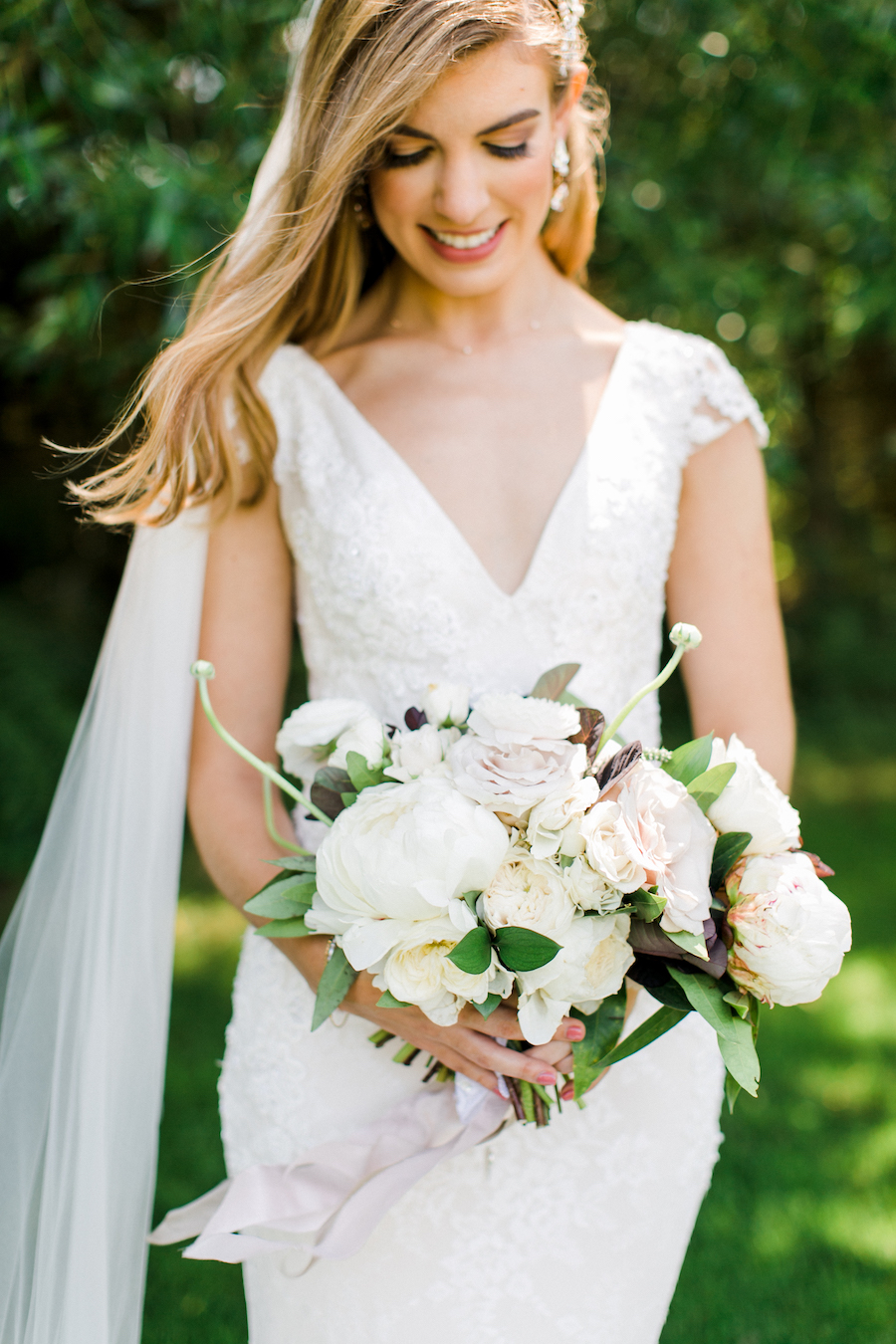 A bride smiling at her bouquet