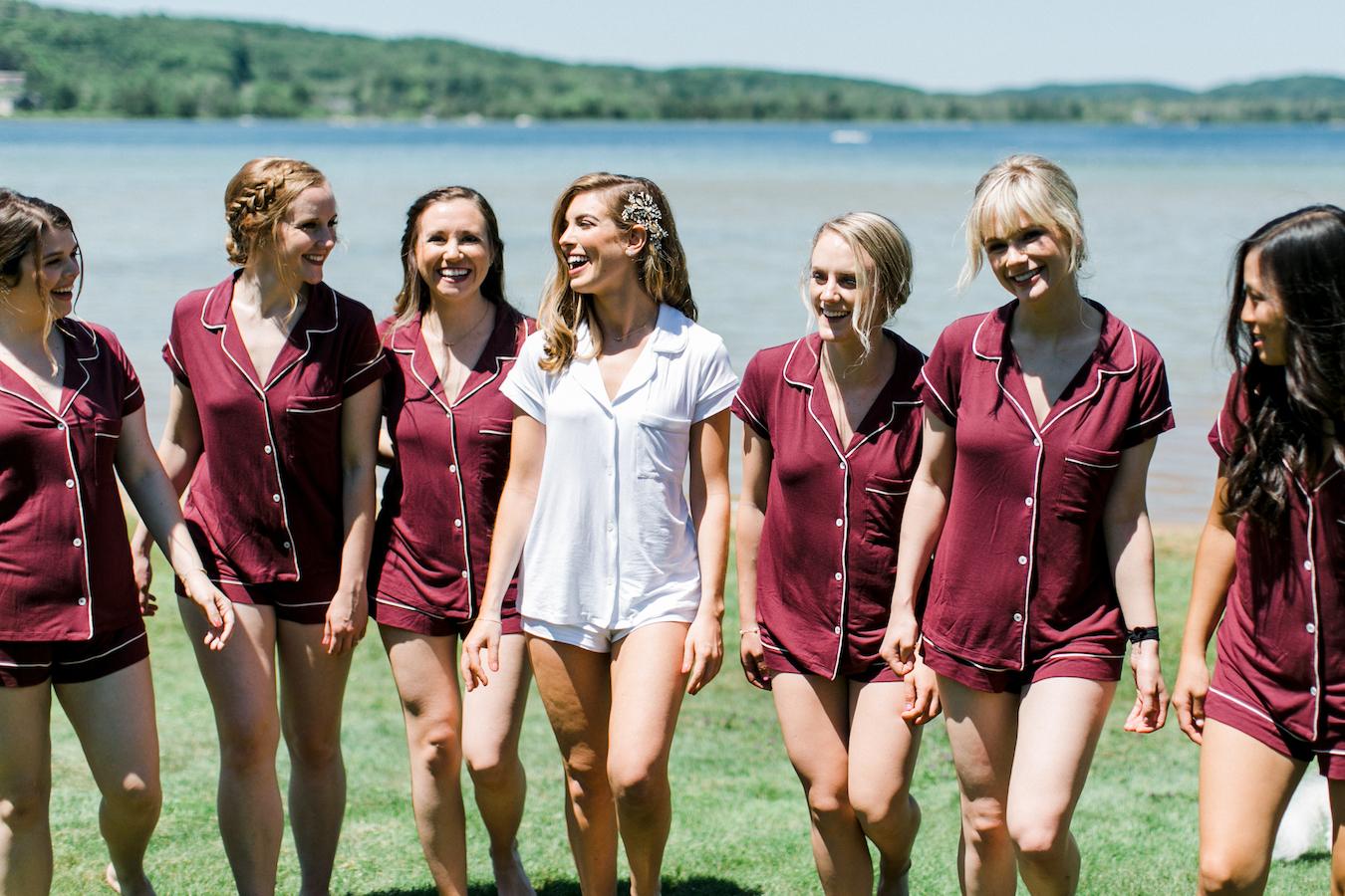 Bride and bridesmaids smiling at Deer Lake, MI