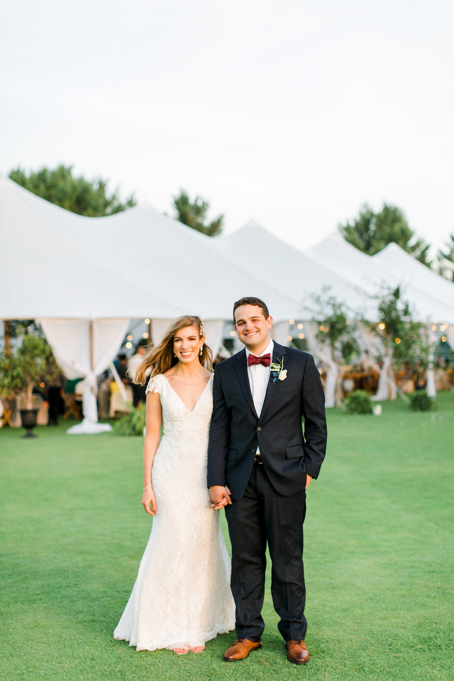 A couple smiling in front of their wedding tent