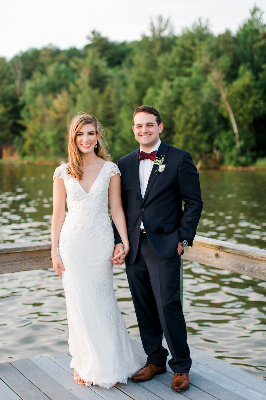 A couple smiling at the camera at their lakeside wedding