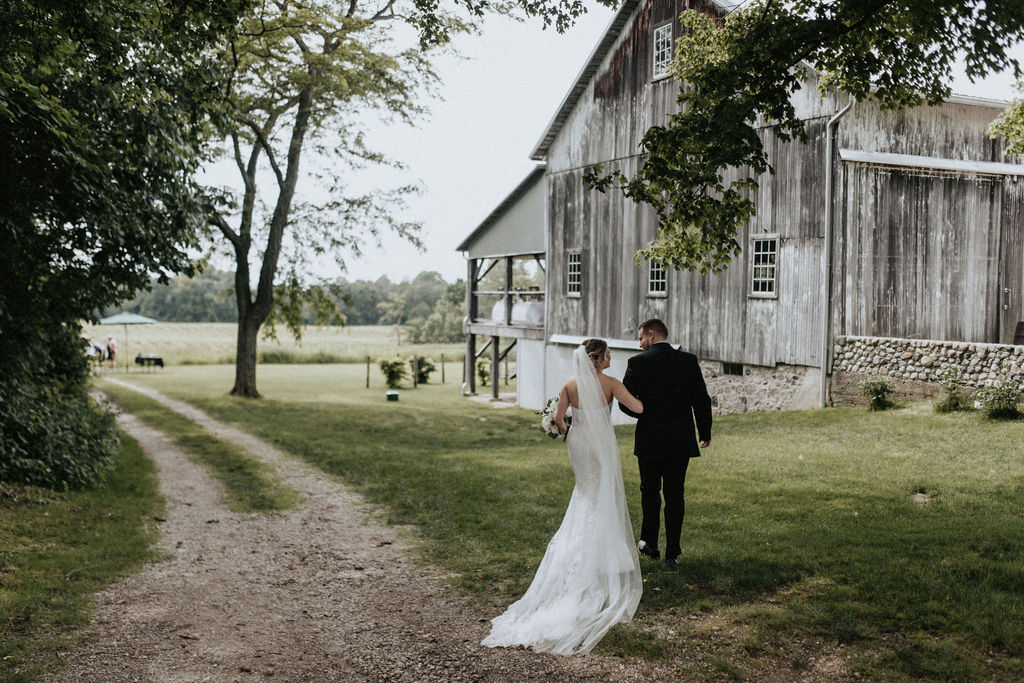 A couple walking to the barn during their Hidden Vineyard Wedding Barn wedding.