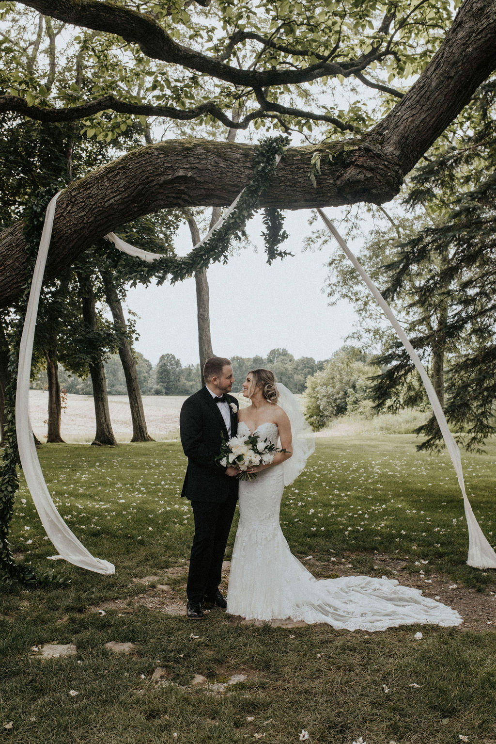A couple smiling in front of their ceremony tree