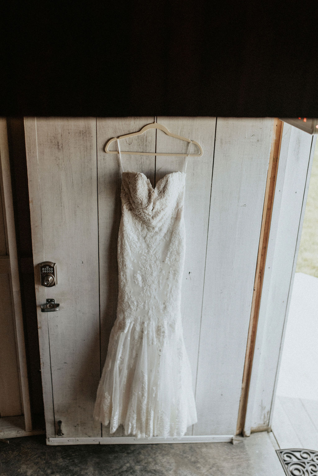 A bridal gown hanging on a barn door.