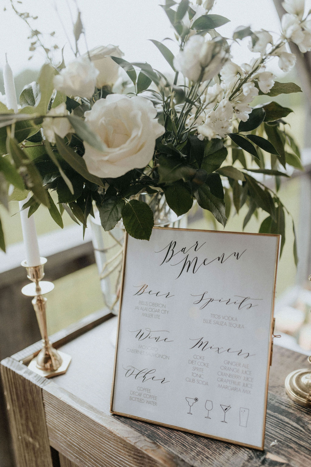 A bar menu with white flowers and greenery.