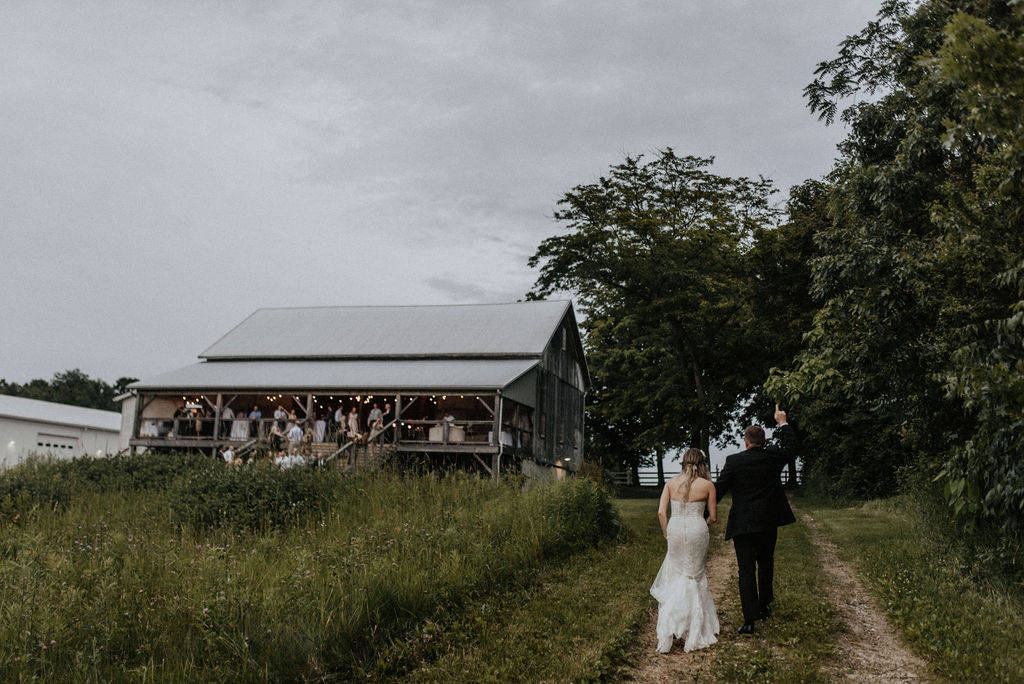 A couple walking to their Hidden Vineyard Wedding Barn wedding