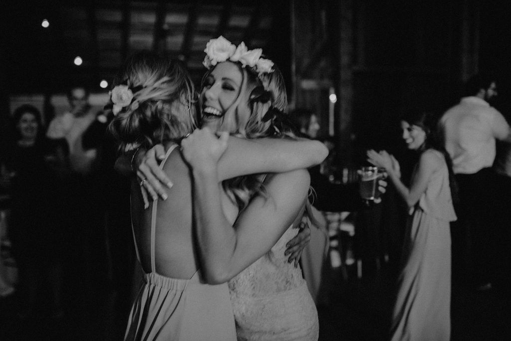 A bride and her sister dancing