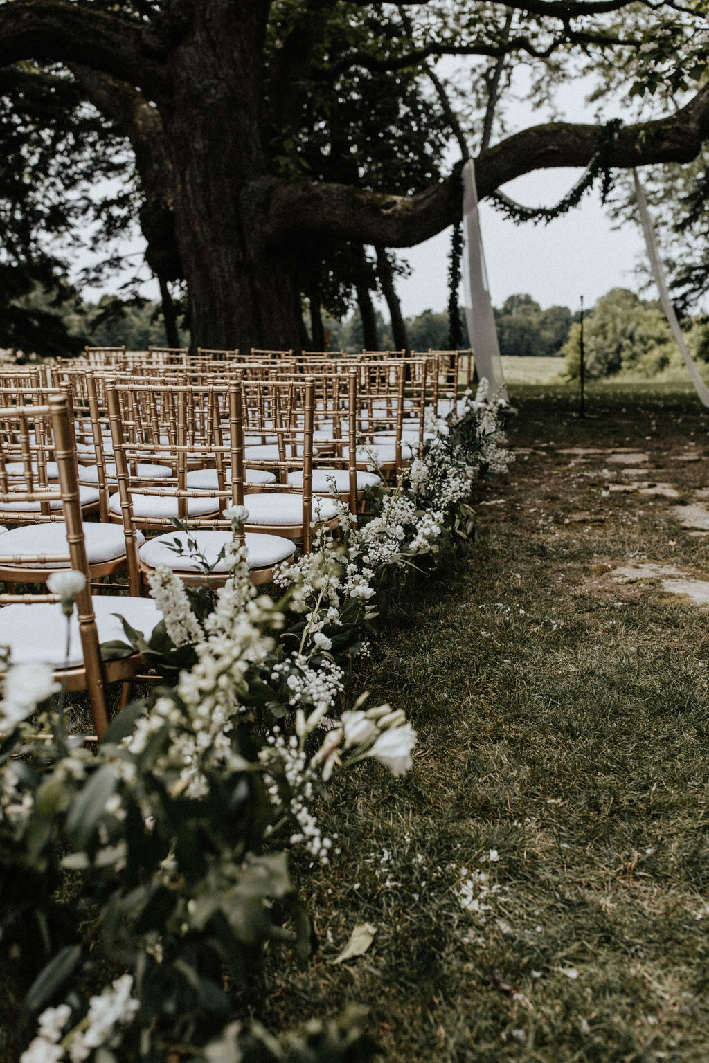 Flowers lining the edge of the aisle at an outdoor ceremony