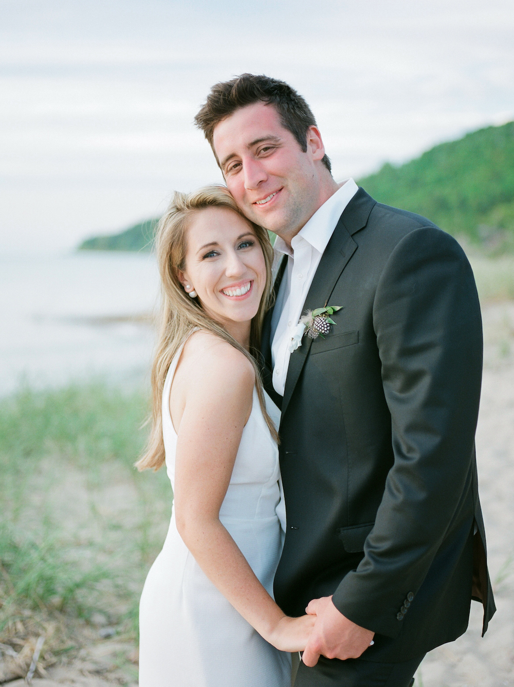 A couple smiling on the beach in Glen Arbor, Michigan