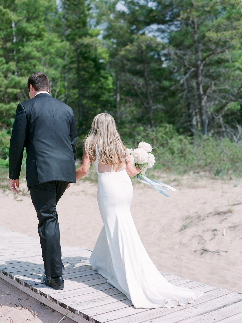 A couple walking off the beach after their wedding