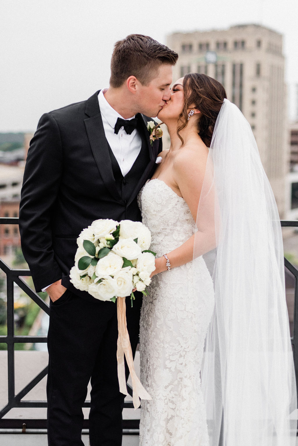 A couple sharing a kiss before their downtown kalamazoo wedding