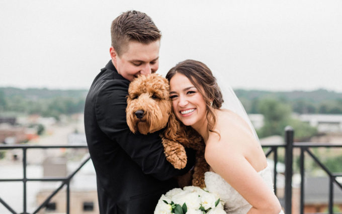 A couple smiling with their dog before their Downtown Kalamazoo wedding ceremony