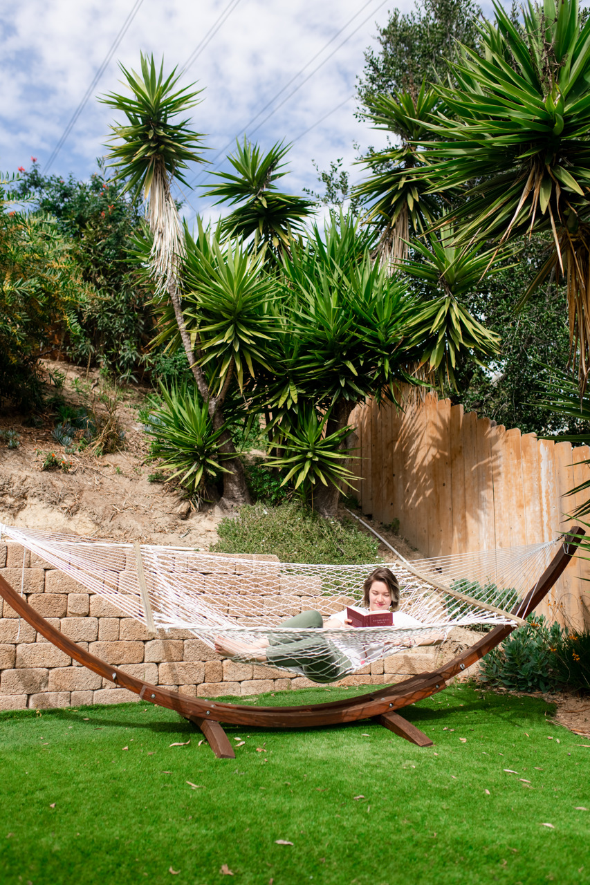 A woman reading a book in a hammock