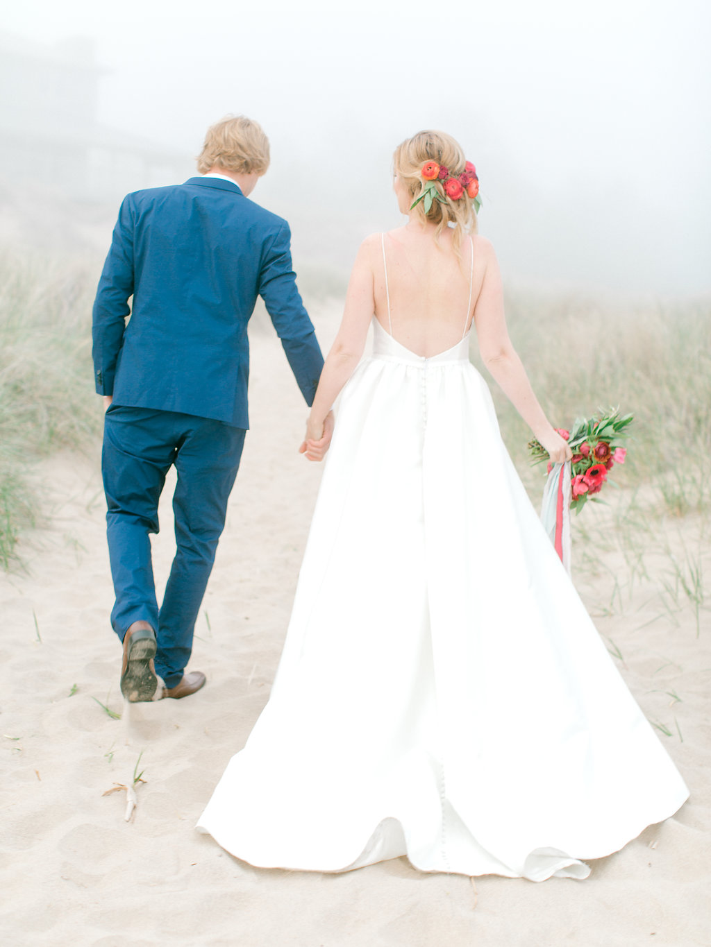 Couple holding hands during their beach wedding in Michigan