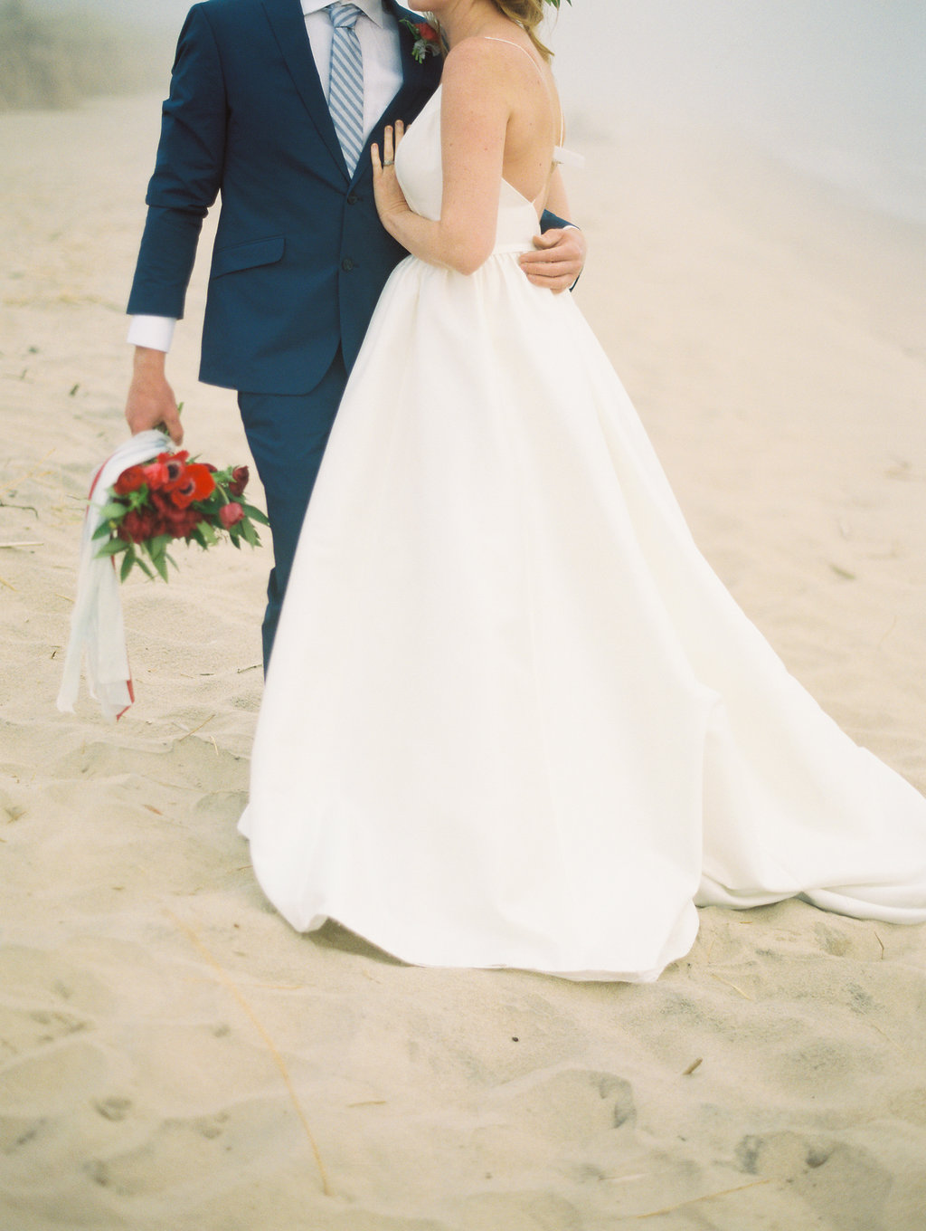 Couple hugging during their Lake Michigan wedding on the beach