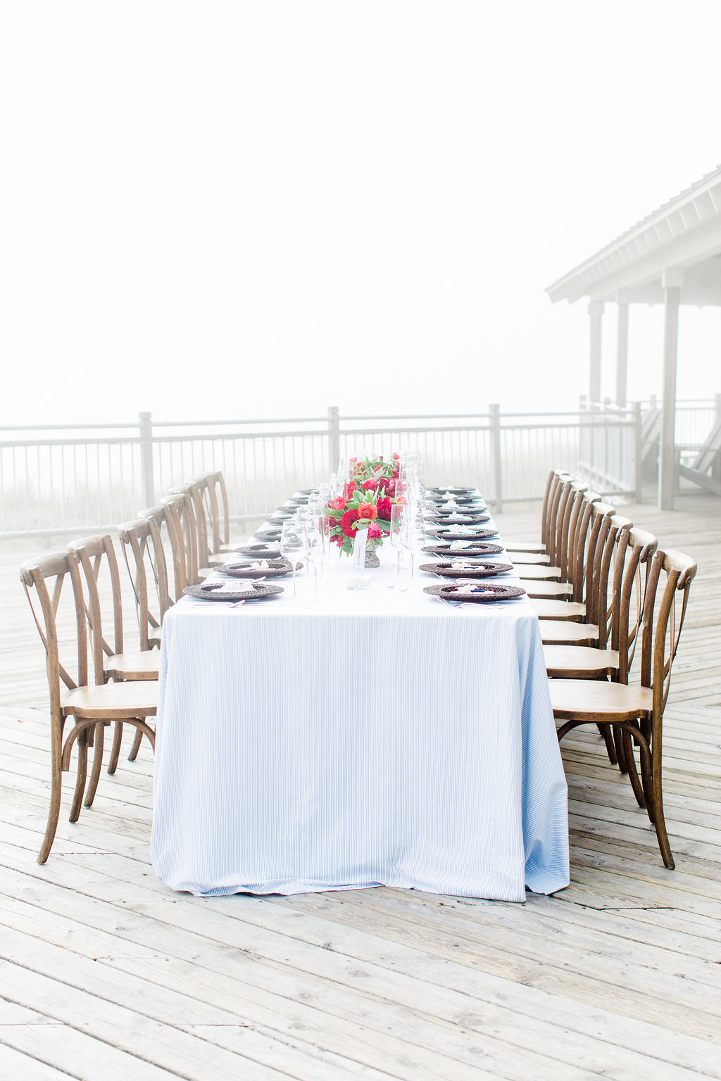 Table set on a deck for a misty lakeside wedding