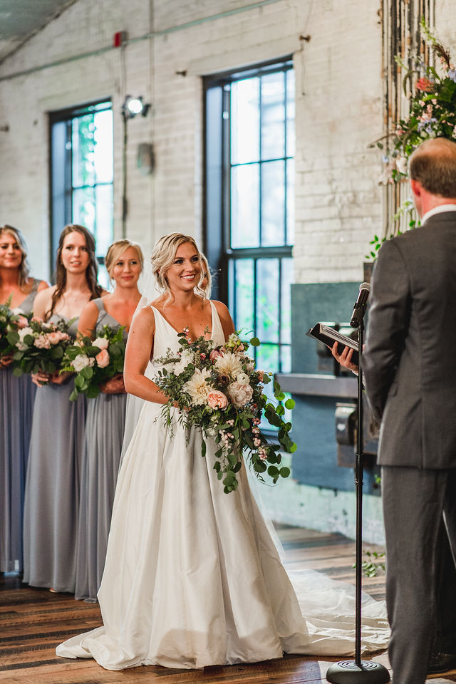 Bride smiling at her groom while exchanging vows