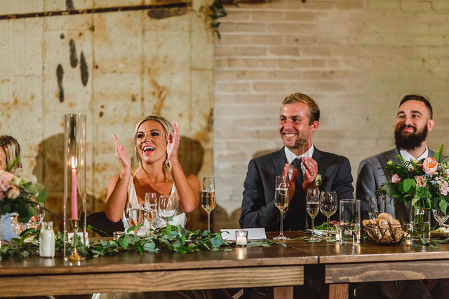 Bride and Groom clapping at head table during speech