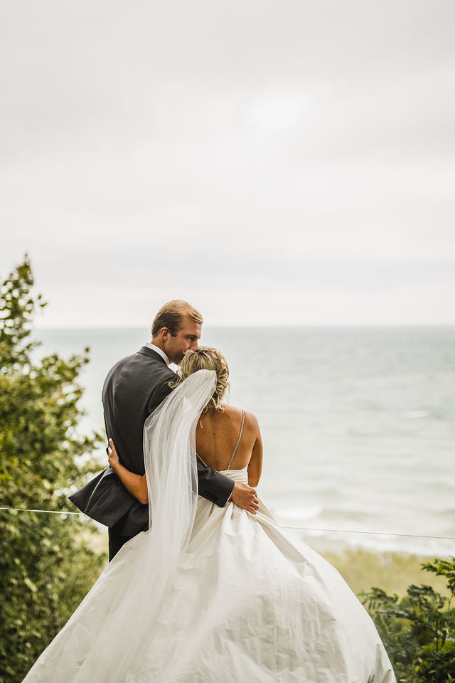 Groom kissing brides forehead with Southwest Michigan wedding background
