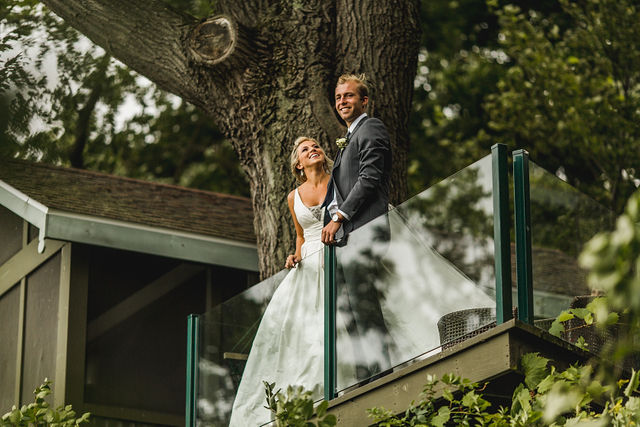 Bride and groom smiling on balcony before Southwest Michigan wedding