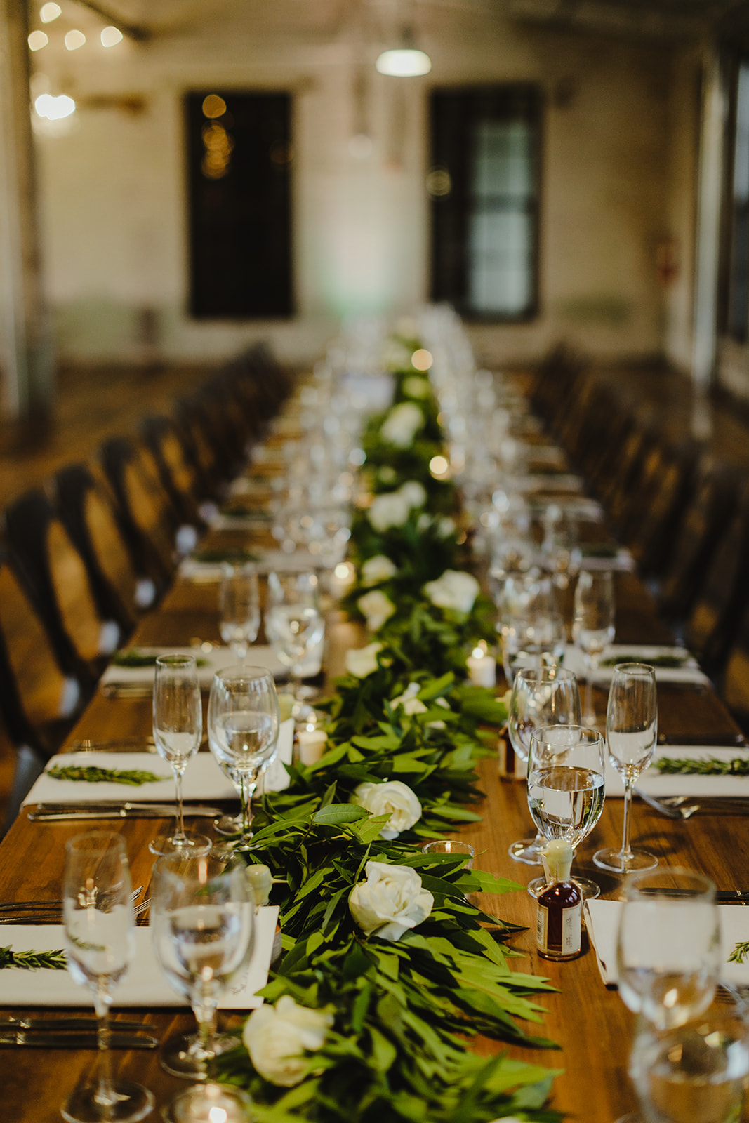 Tables set for greenery for a Journeyman Distillery wedding