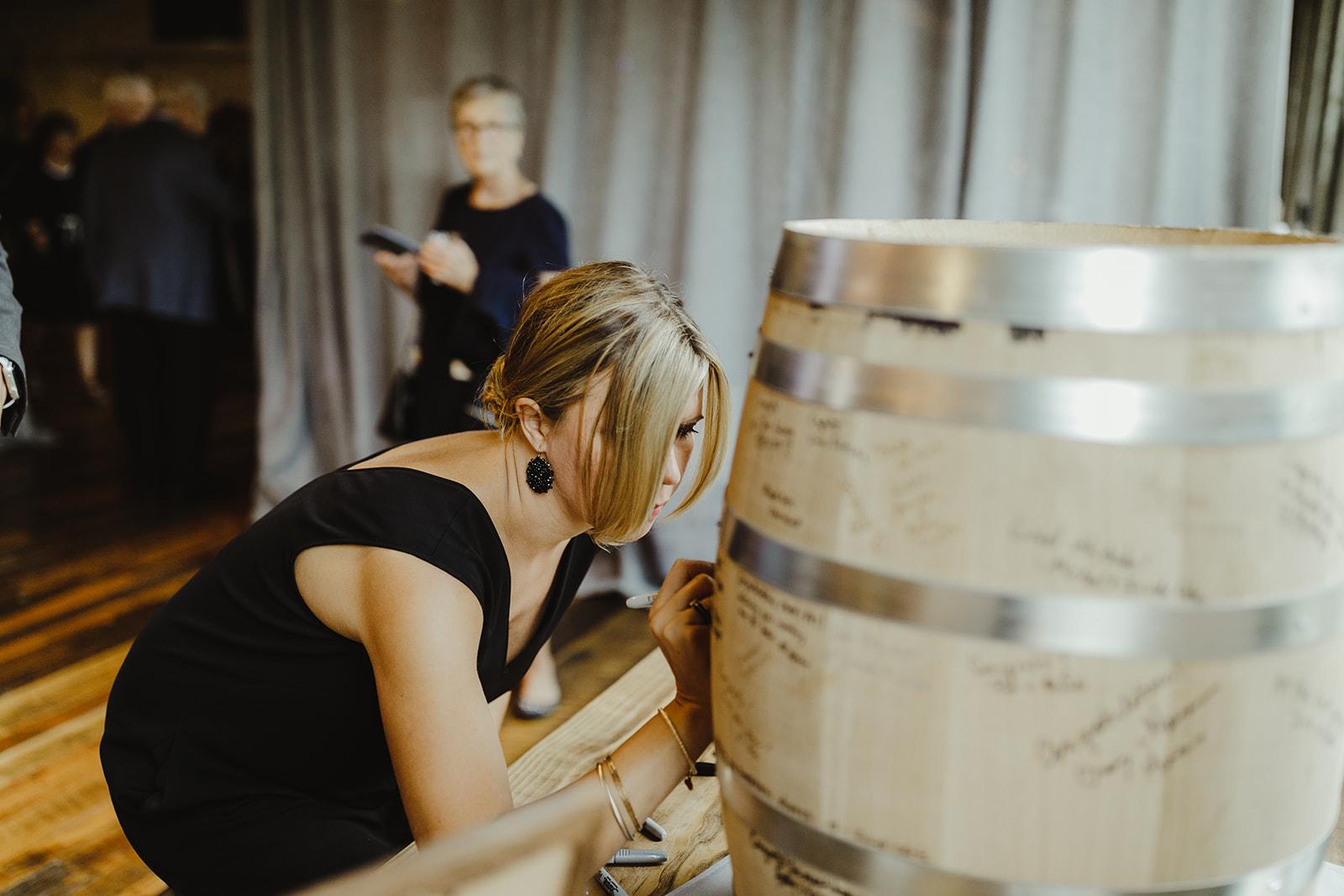 Guests signing a barrel guest book