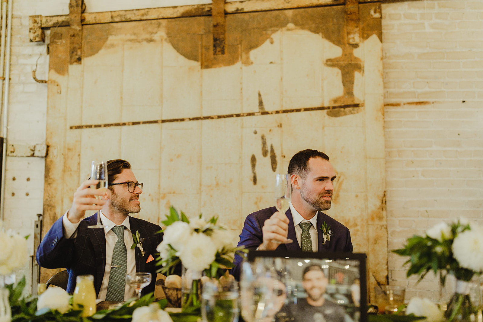 Grooms toasting their friends