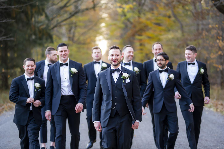 Groom and groomsman walking on road