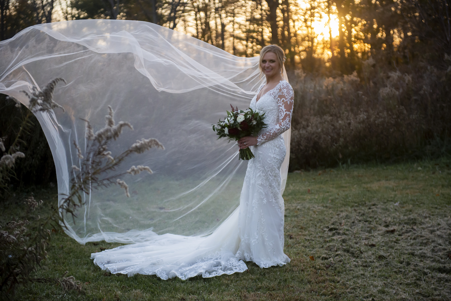 Bride's veil flowing in field for rustic Michigan wedding