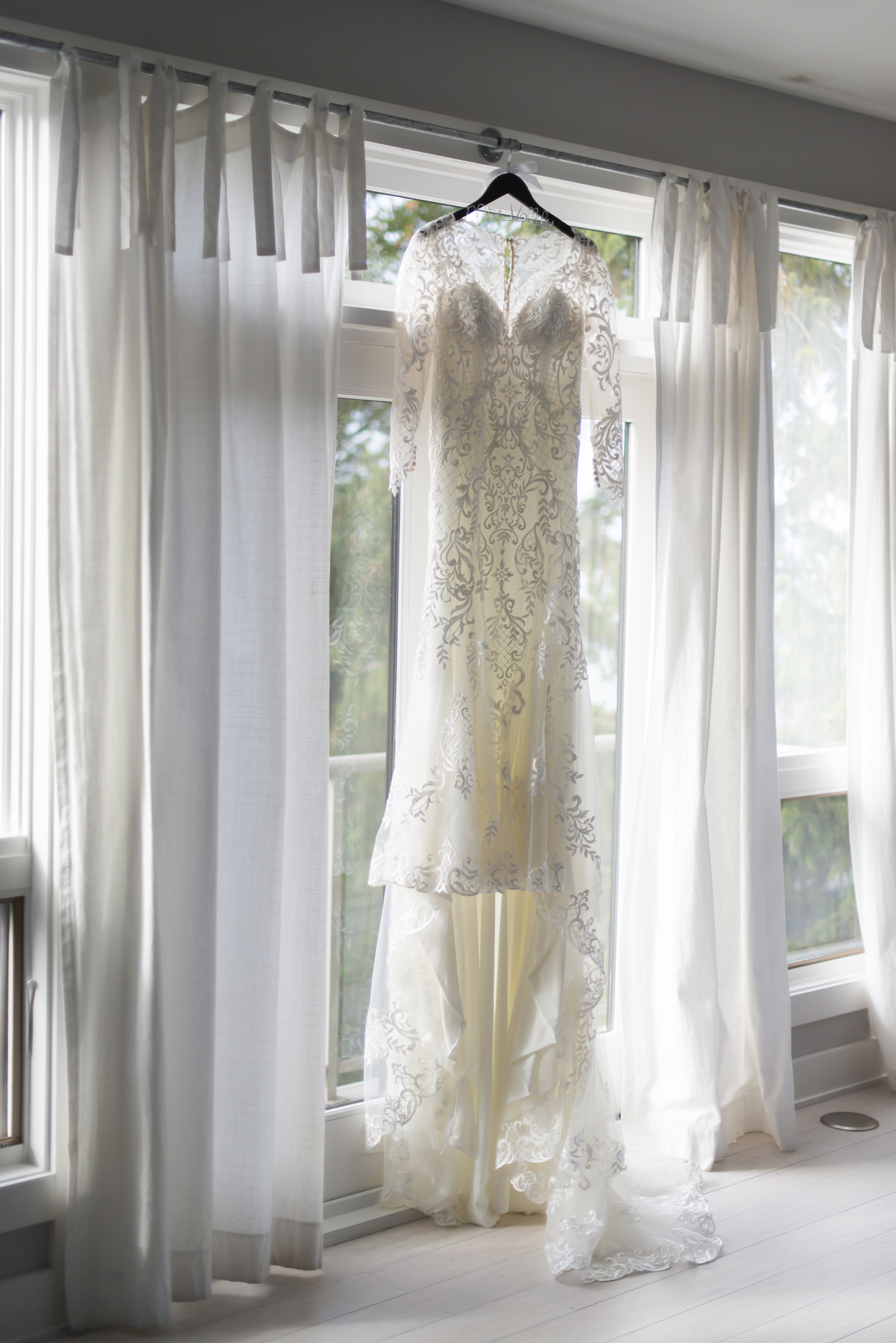 Bridal gown hanging before rustic Michigan wedding