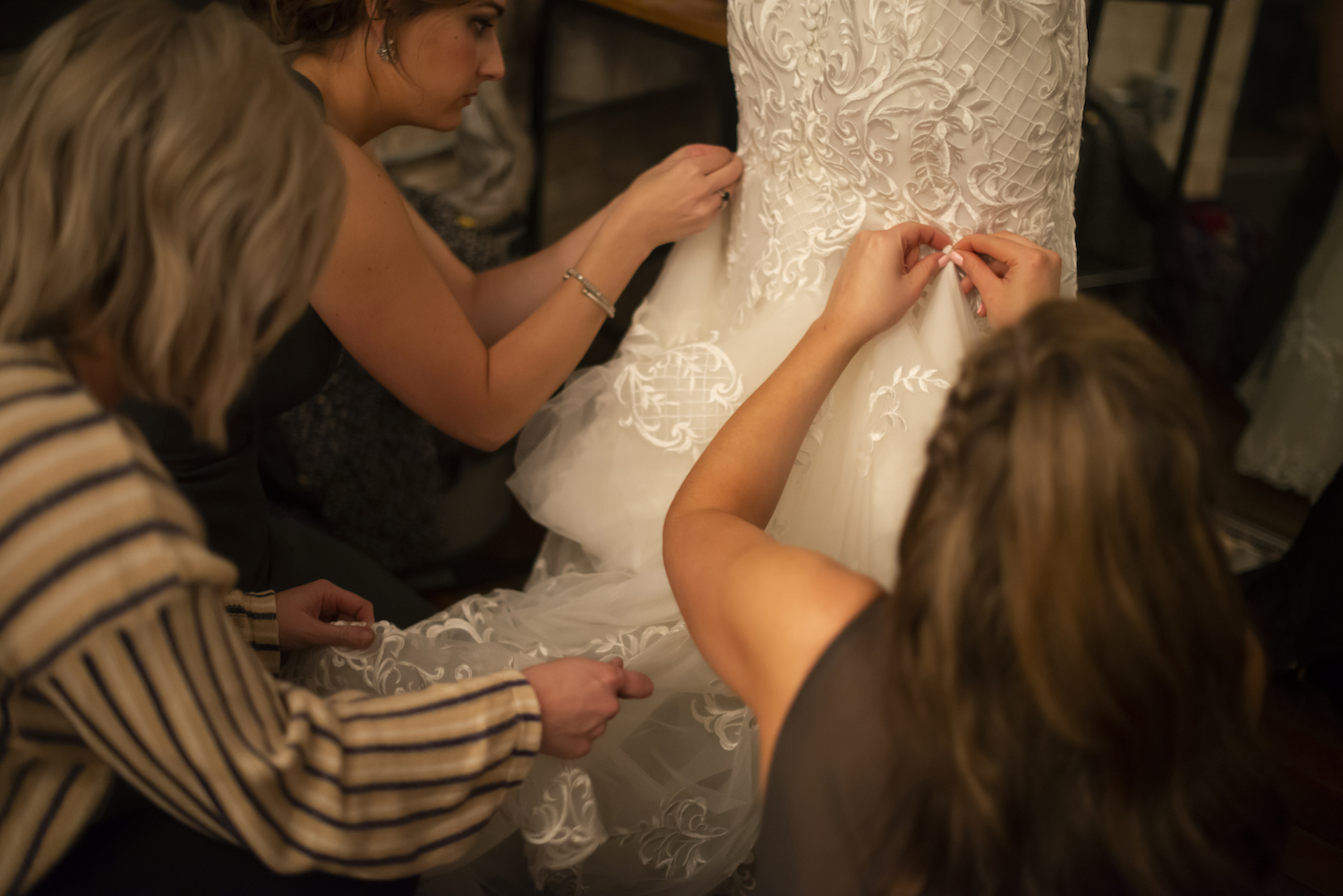 Bride's dress being buttoned up in back