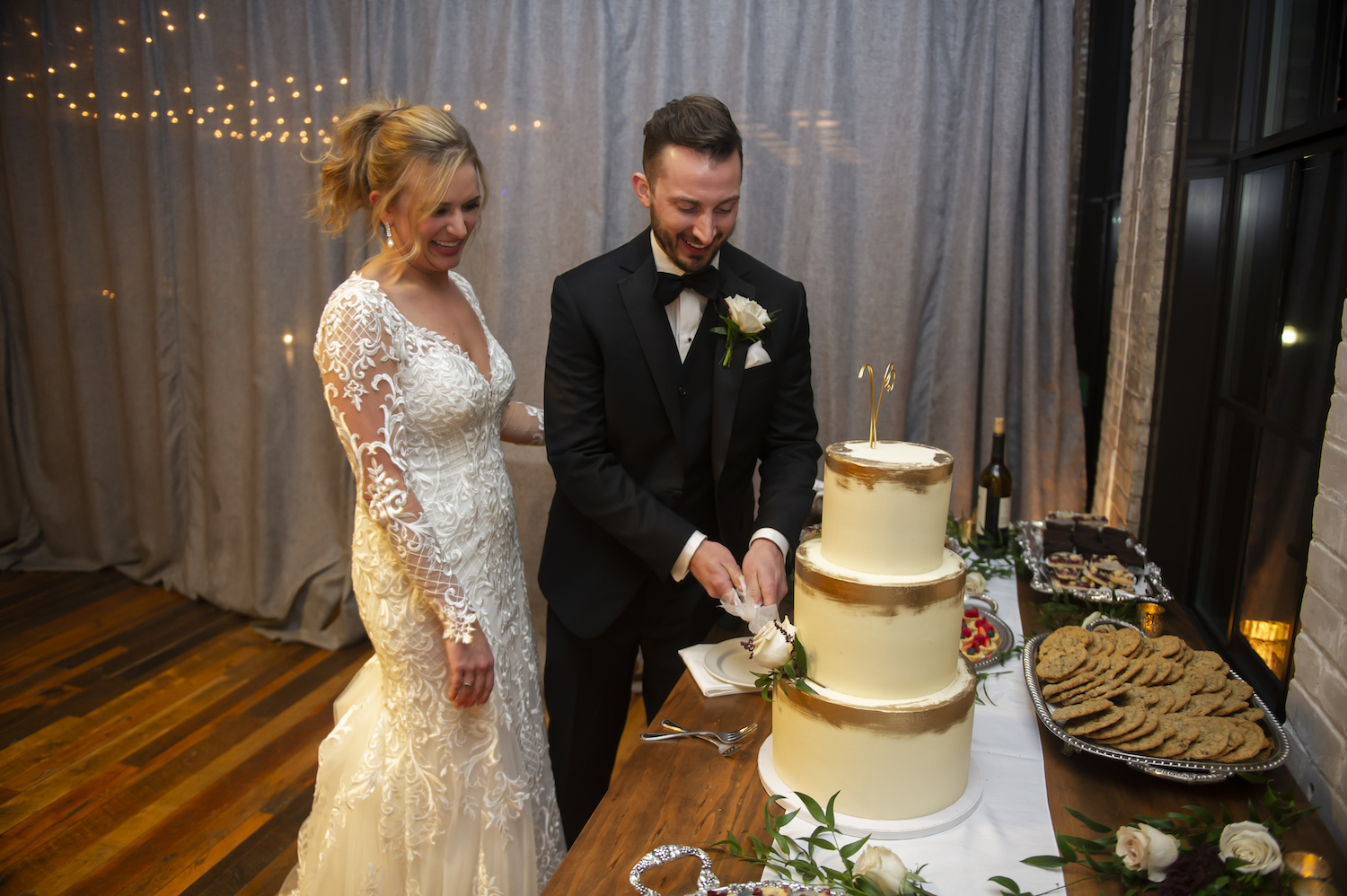 Bride and groom cutting cake smiling