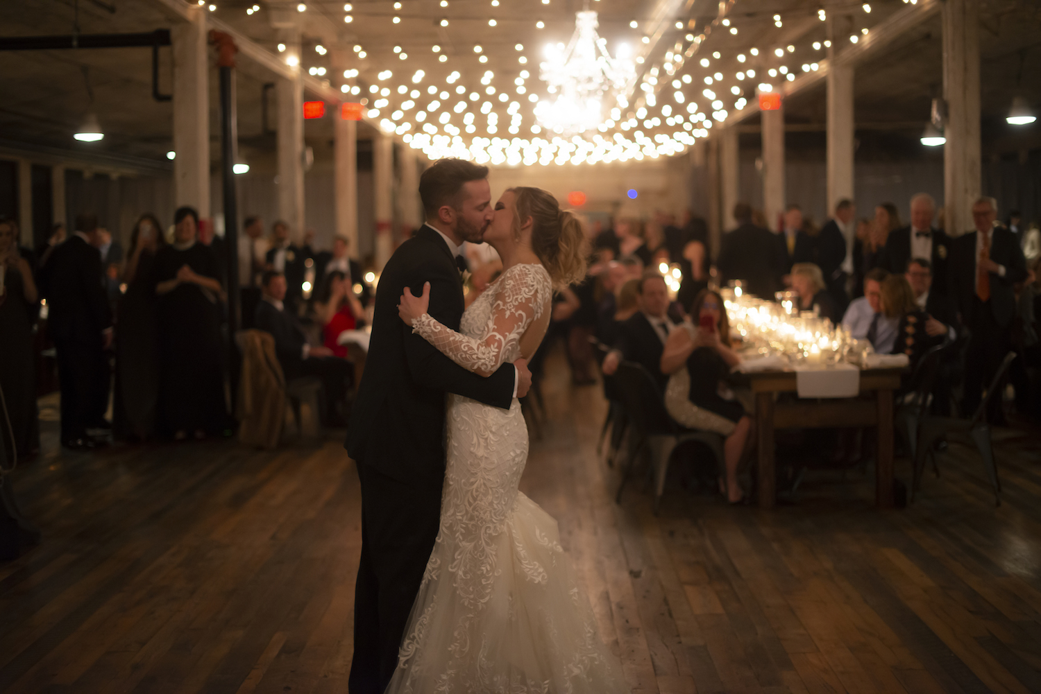 Bride and groom kissing during first dance at rustic Michigan wedding