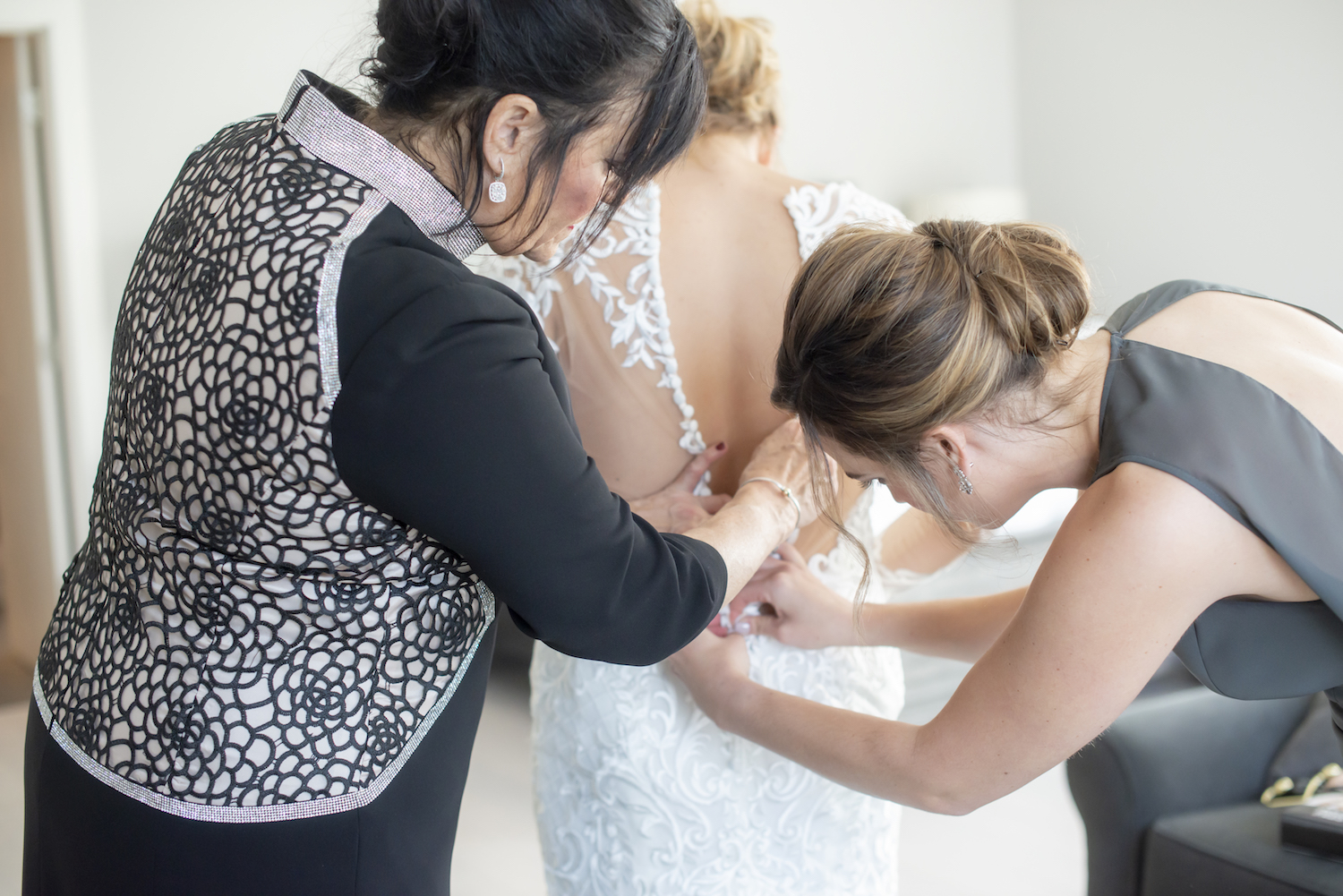 Mother of Bride buttoning bride's dress