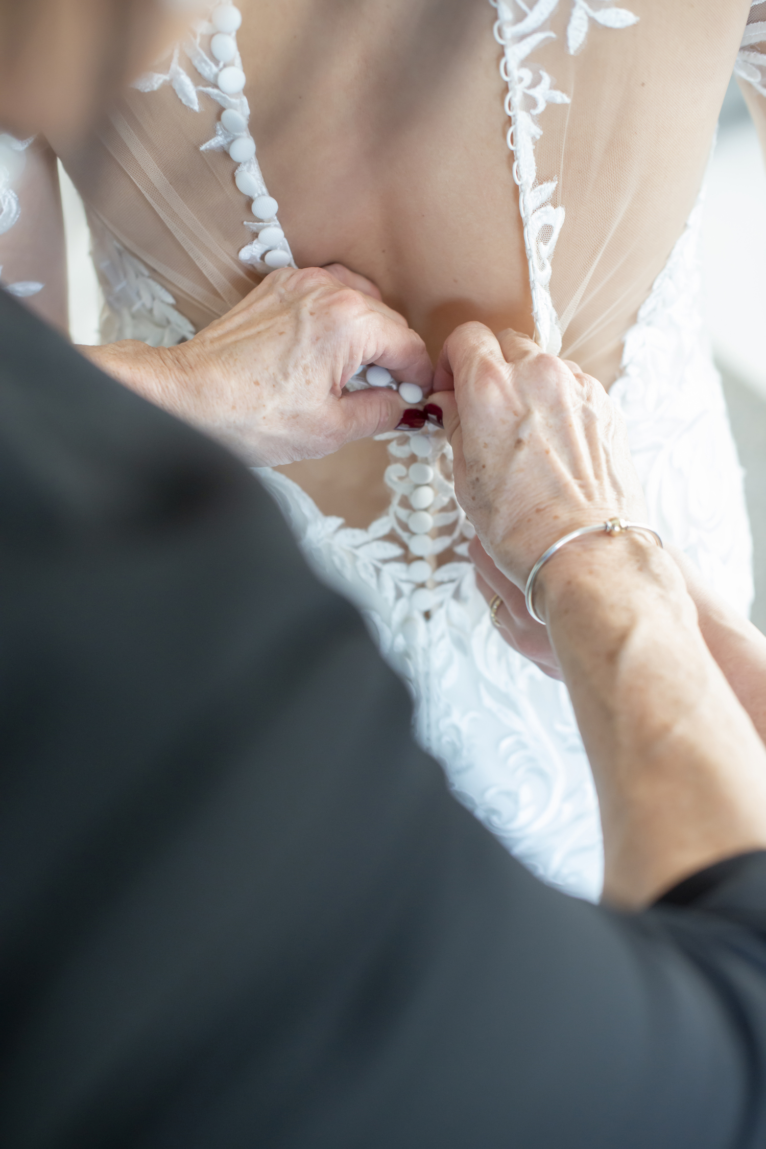 Mother of bride finishing buttoning bride's gown