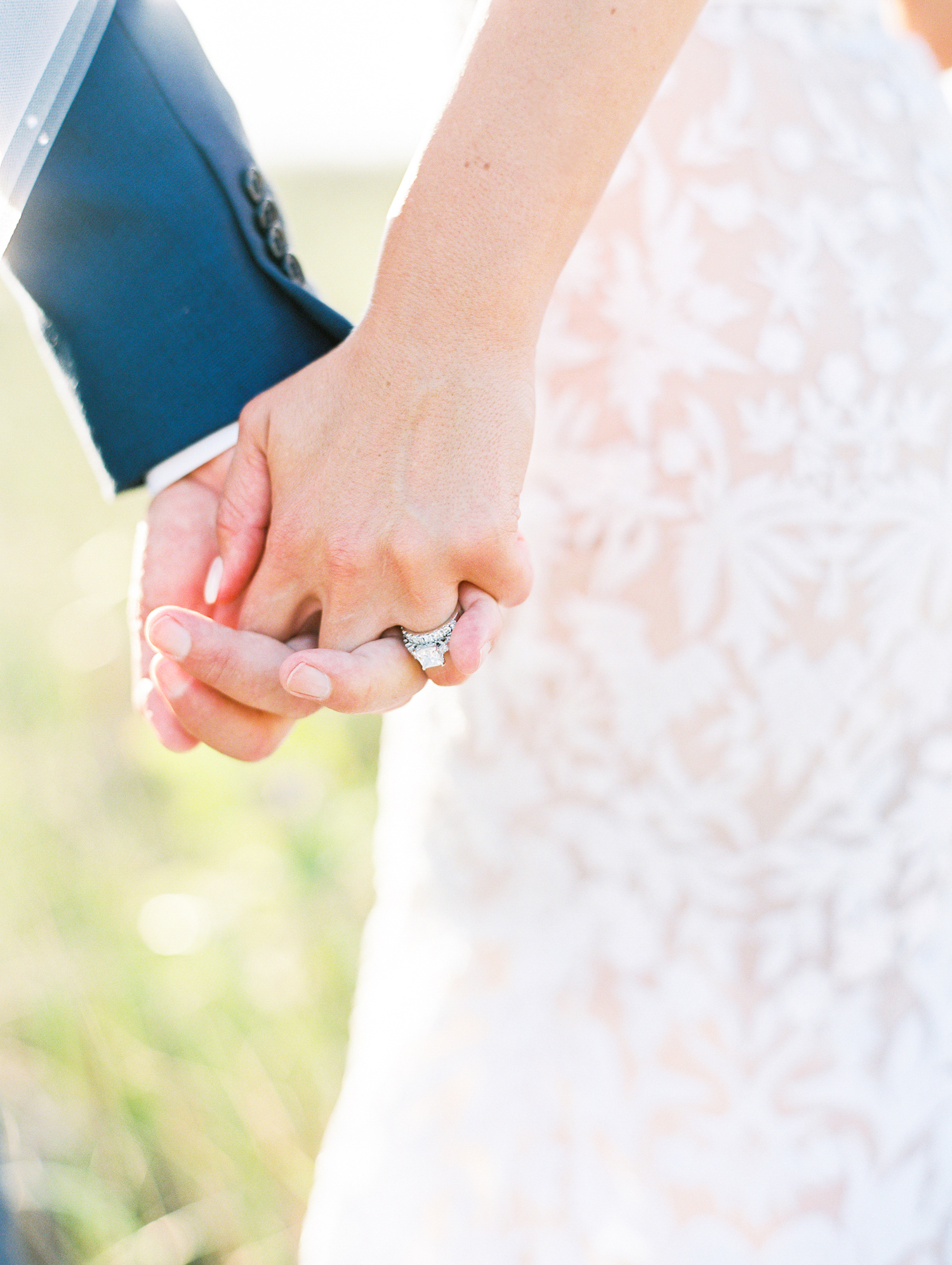 Holding hands at apple blossom resort wedding