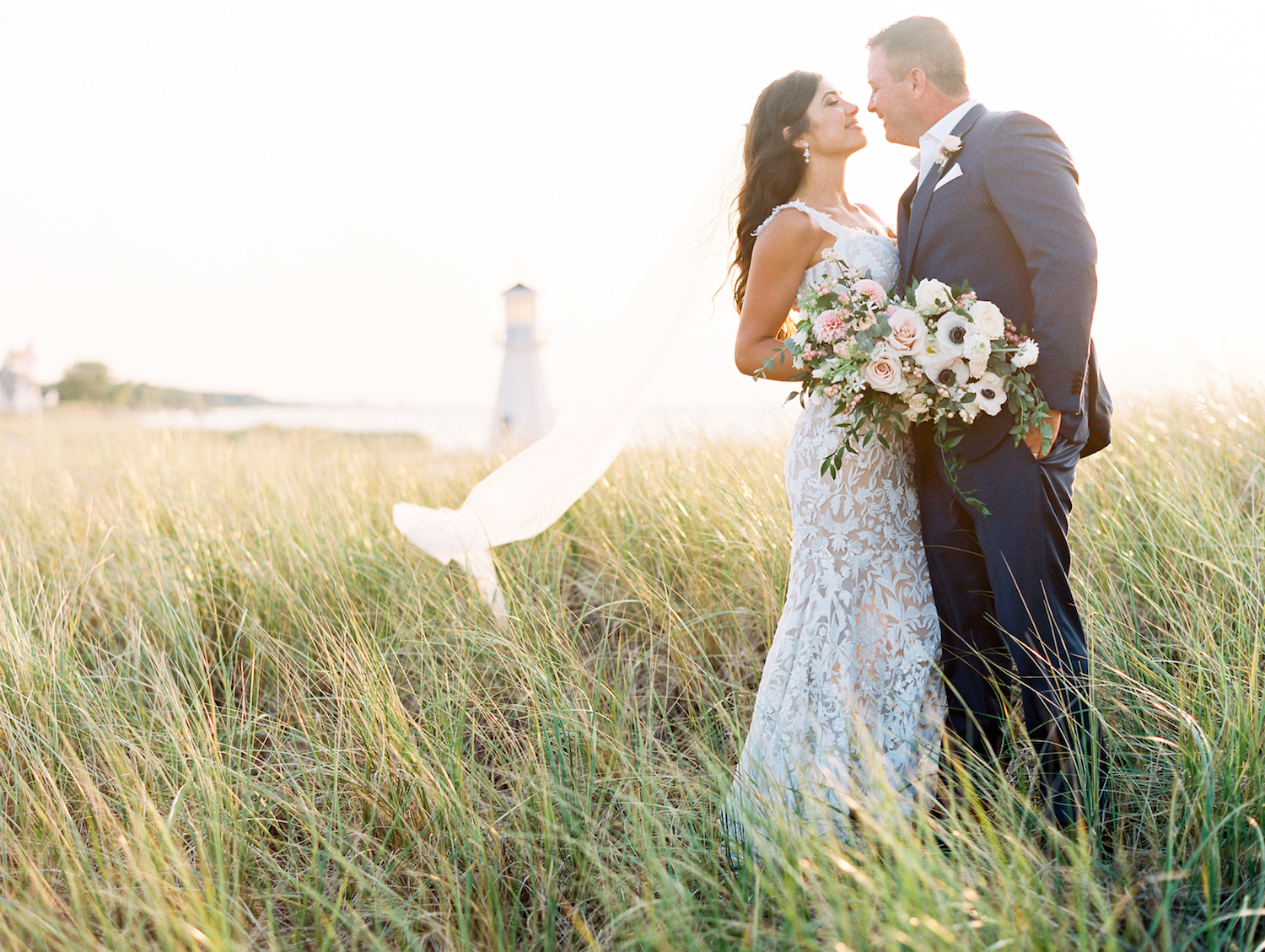 Bride and groom smiling with lighthouse in background