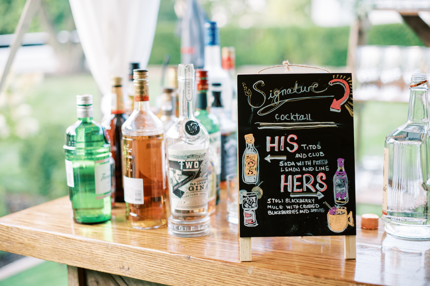 Signature drinks sign with alcohol bottles at apple blossom resort wedding