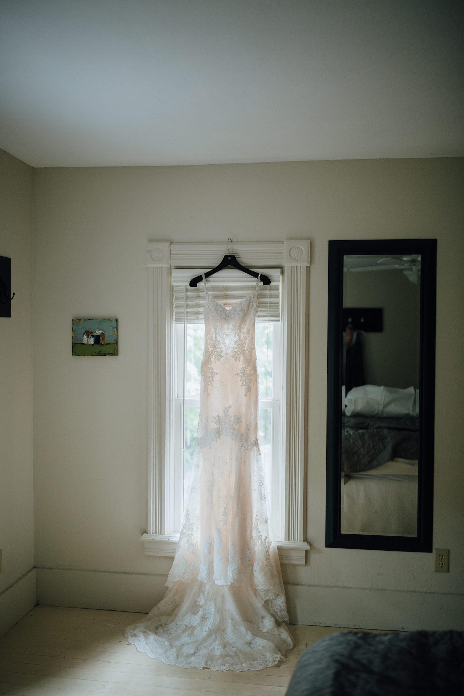 Bride's dress hanging on window at Aurora Cellars wedding