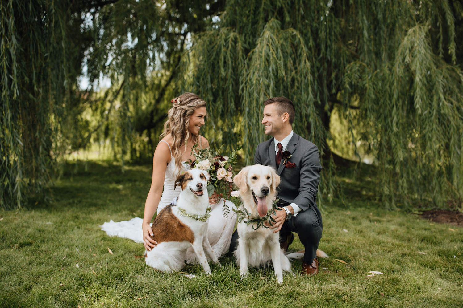Bride and Groom smiling at each other with dogs
