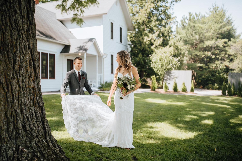 Groom helping bride with dress at Aurora Cellars wedding