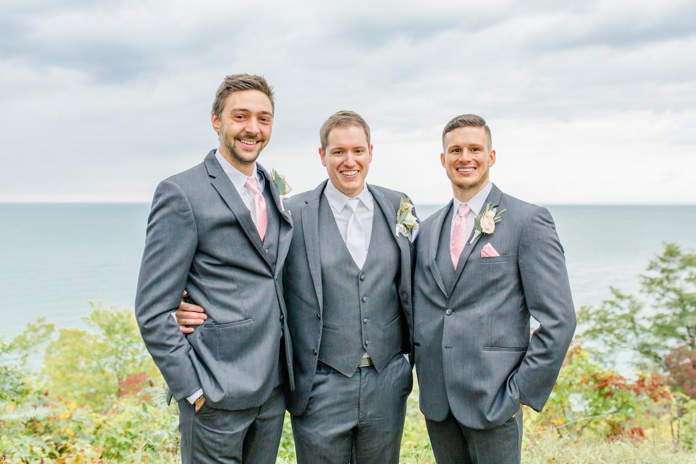 Groomsmen smiling at the lakehouse wedding