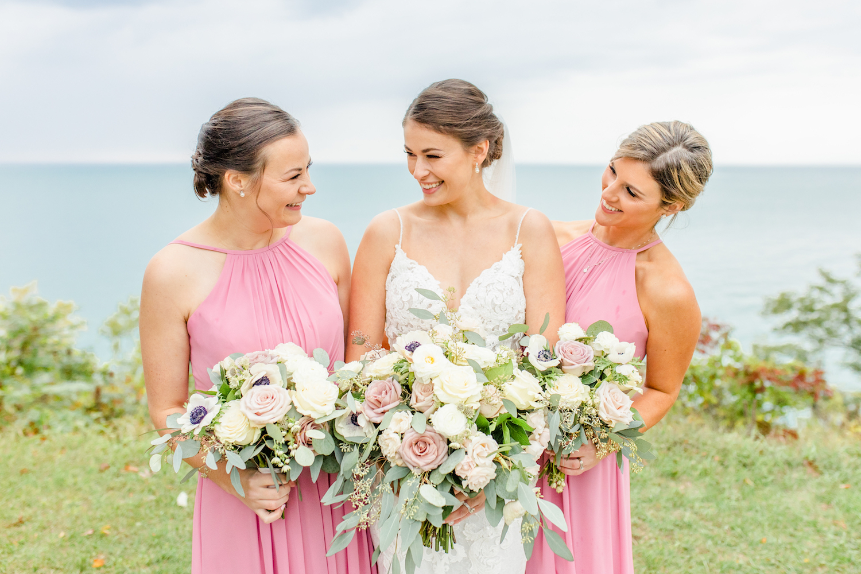 Bride and bridesmaids smiling at the lakehouse wedding